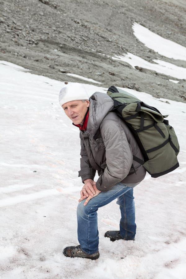 成熟站立在山溜滑陡坡和看照相机的白种人远足者 免版税库存图片