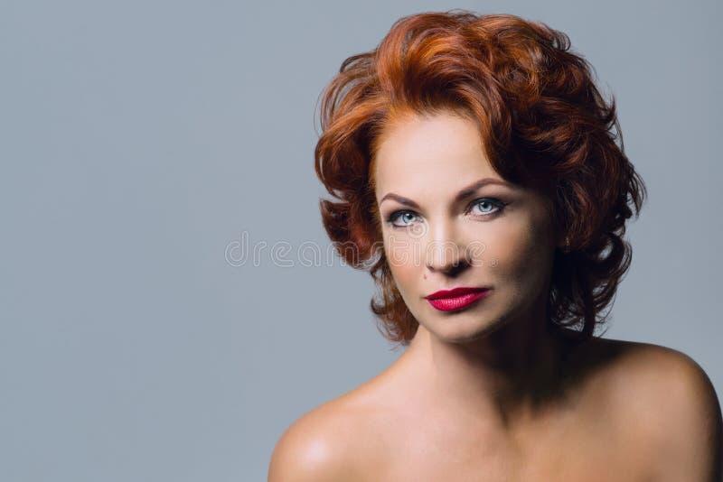 成熟红头发人妇女特写镜头画象有明亮的红色嘴唇的,蓝眼睛 有晚上构成发型光秃的肩膀lo的女性 库存照片