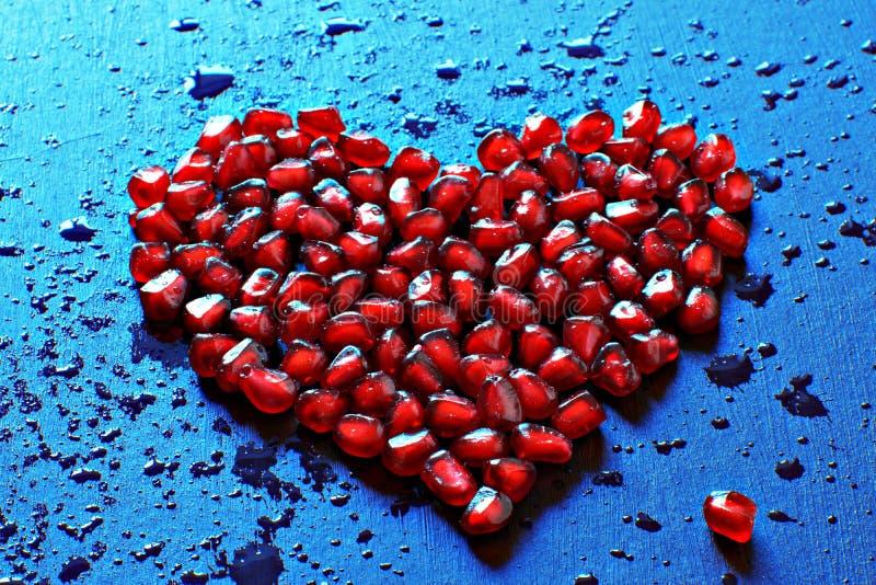 成熟红色石榴种子的心脏在蓝色背景的,飞溅,水,健康食物污点和滴  库存照片