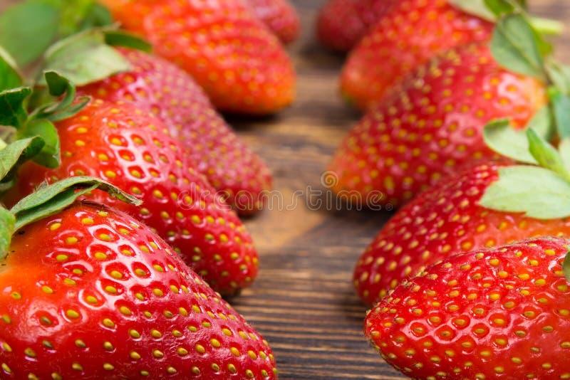 成熟红色草莓两行,在一个木板 免版税图库摄影