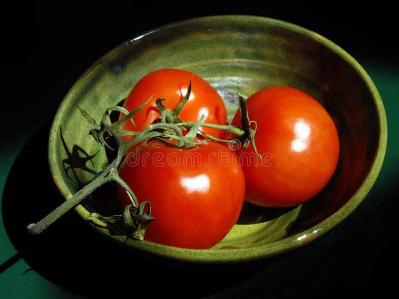 成熟红色蕃茄三重奏在藤的在日本瓦器碗 免版税库存照片