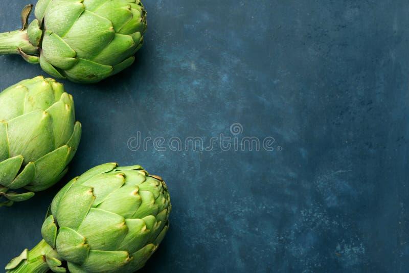 成熟绿色朝鲜蓟堆在深蓝背景的 创造性的食物海报 r 地中海西班牙烹调 库存照片