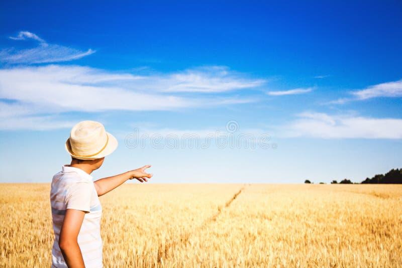 成熟耳朵的领域的农夫陈列在距离的一个手指 免版税库存照片