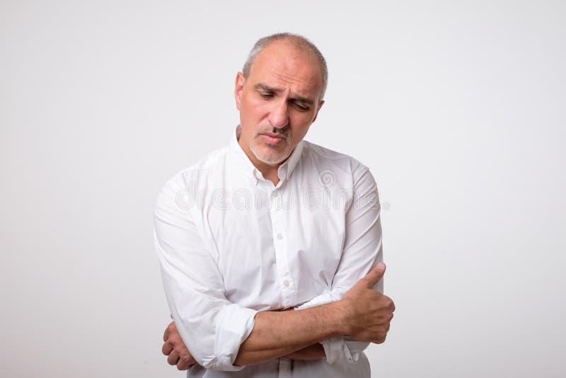 成熟英俊的人画象白色衬衣的有在面孔的严肃和哀伤的表示的 库存图片