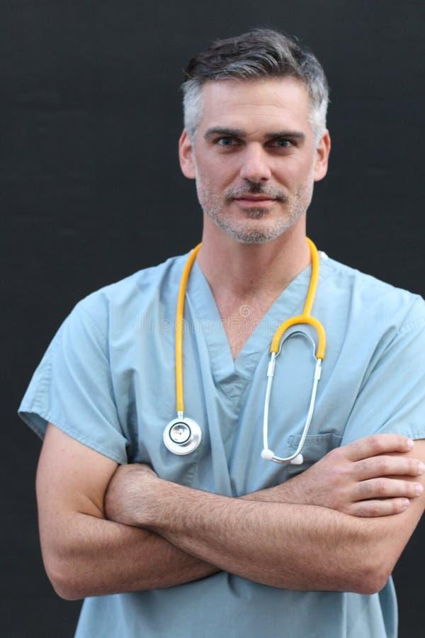 成熟英俊的医疗保健工作者画象隔绝与横渡的胳膊 免版税库存照片