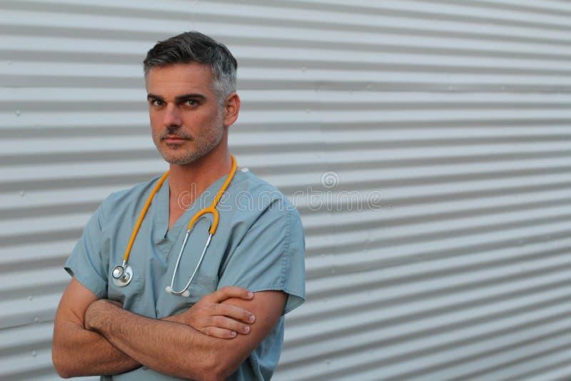 成熟英俊的医疗保健工作者画象隔绝与横渡的胳膊 免版税图库摄影