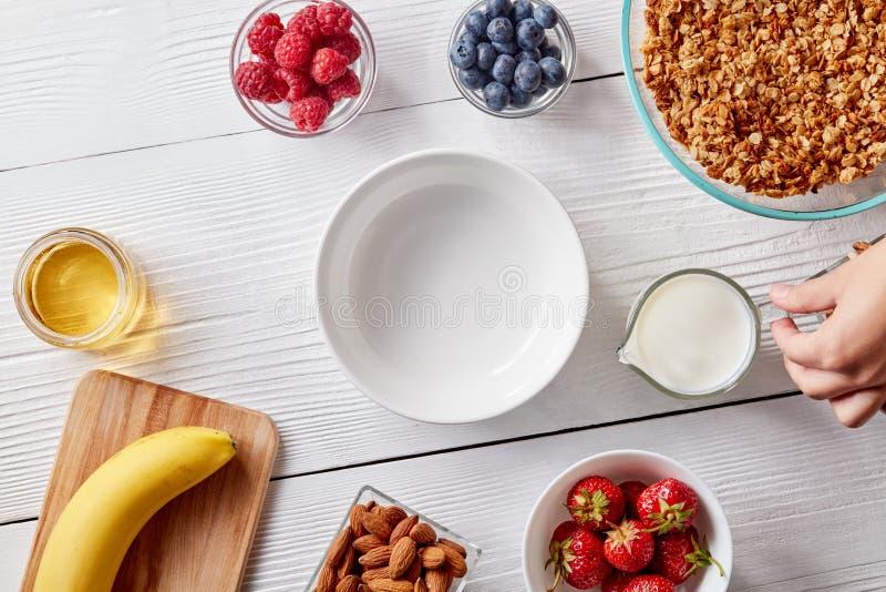 成熟莓果、格兰诺拉麦片、坚果、蜂蜜和一块空的板材在一张白色木桌上 妇女` s手拿着一杯牛奶 免版税库存图片