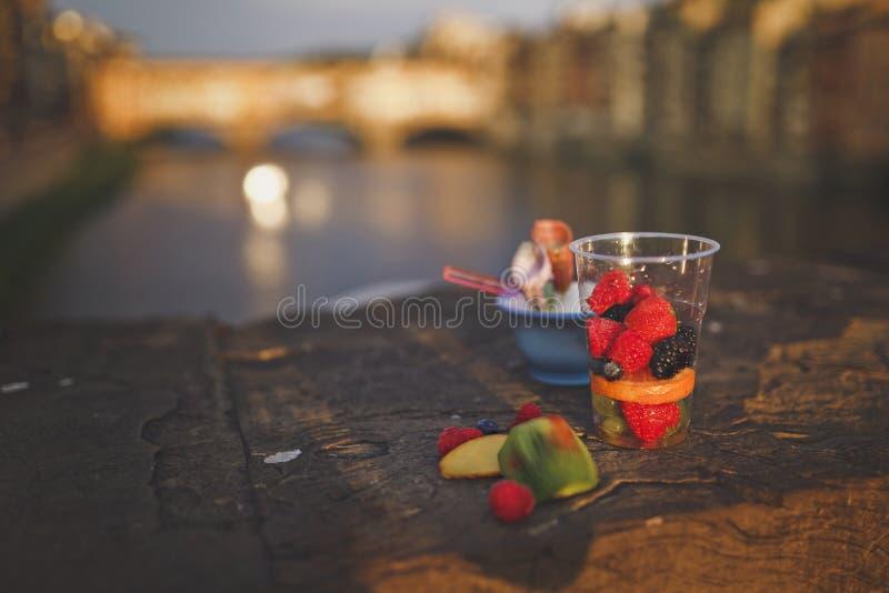 成熟莓果和果子在一个杯子一顿快餐的在城市桥梁的栏杆 免版税库存图片