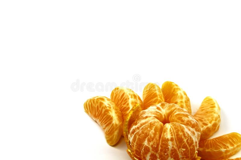 成熟蜜桔说谎在皮肤和在它附近从另一个蜜桔的一点切片在白色背景 图库摄影