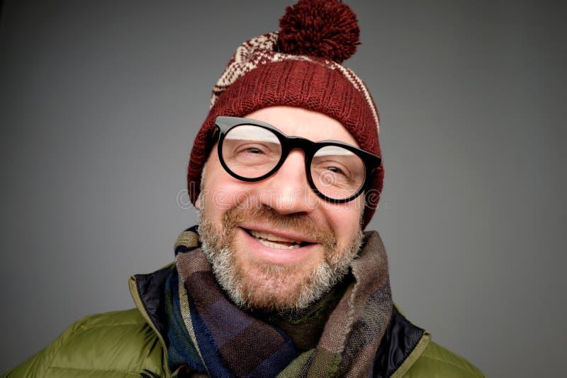 成熟行家人画象玻璃和帽子摆在的 穿温暖的衣裳的微笑的有胡子的人为冬天 库存照片