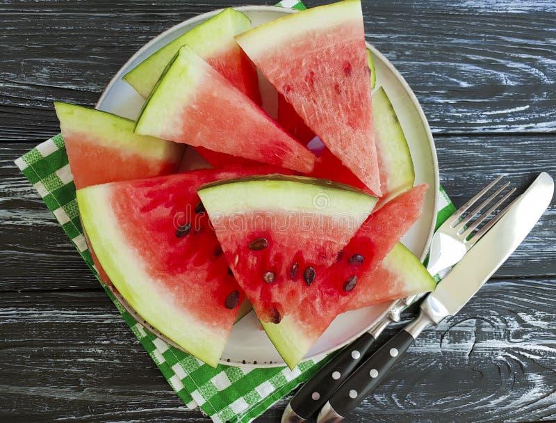 成熟西瓜片,在自然黑木的背景的板材部分夏天有机点心 图库摄影