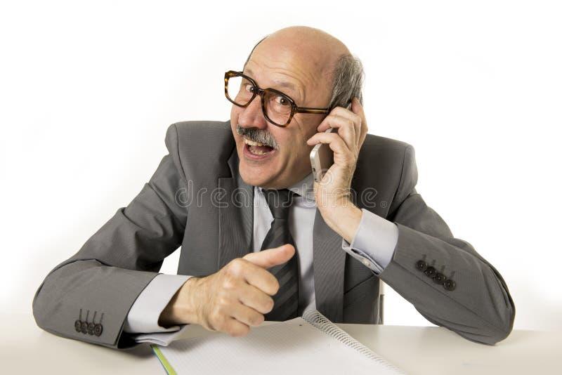 成熟资深商人谈话在手机在办公桌工作愉快和打手势滑稽 免版税库存图片