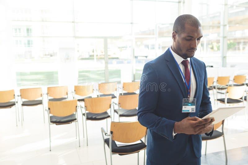 成熟非裔美国人的商人身分在有片剂的会议室 免版税库存照片