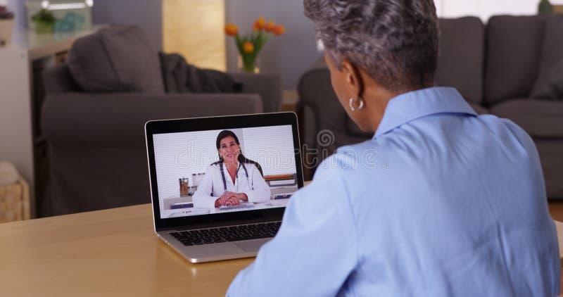 成熟非洲妇女谈话与膝上型计算机的医生 免版税库存图片