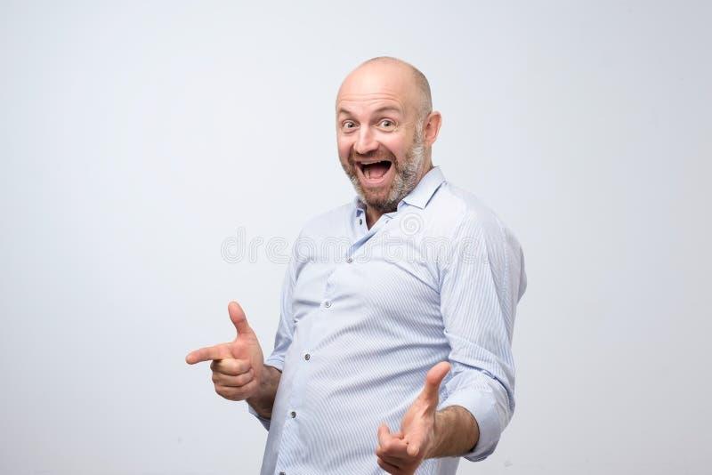 成熟高兴人佩带的白色衬衣指向您 库存照片