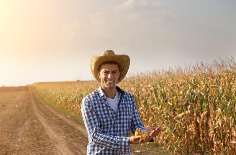草帽农夫_有拿着在领域的草帽的微笑的农夫玉米种子在收割期