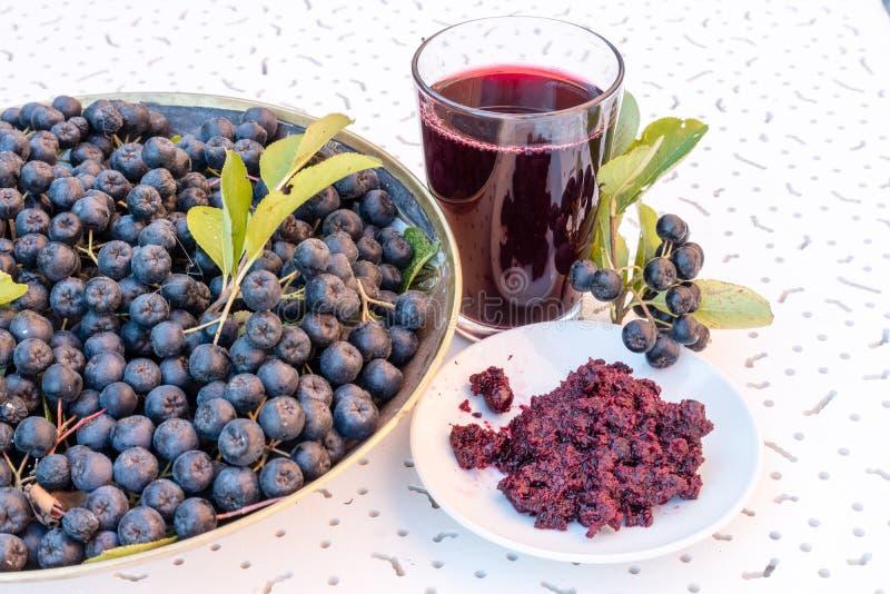 成熟黑堂梨属灌木Aronia melanocarpa新鲜的汁液和果酱特写镜头在玻璃和莓果的在白色织地不很细backgroun的罐 免版税图库摄影