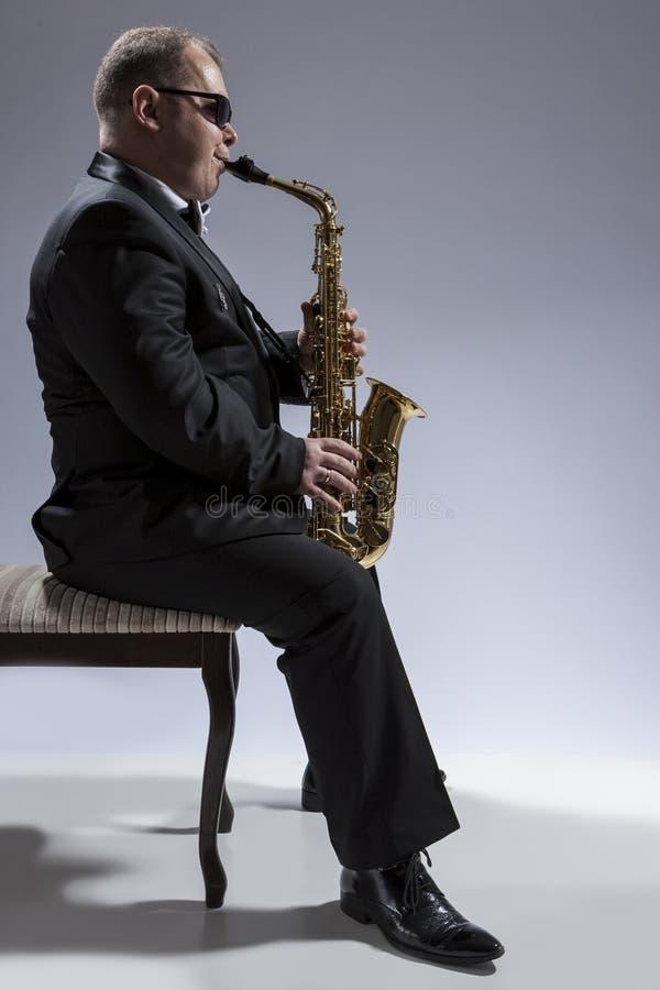 成熟轻松和体贴的白种人萨克管演奏员画象  图库摄影