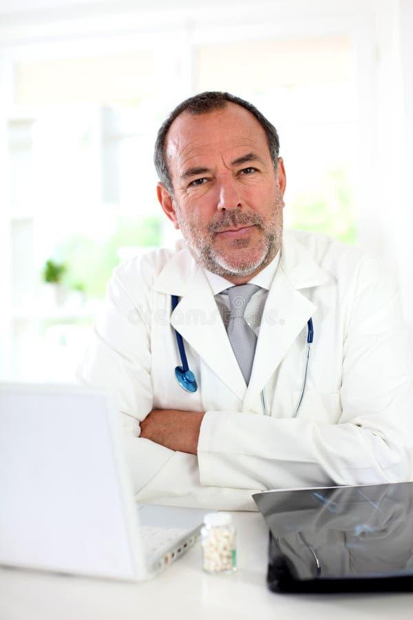 成熟医生在医疗办公室 库存图片