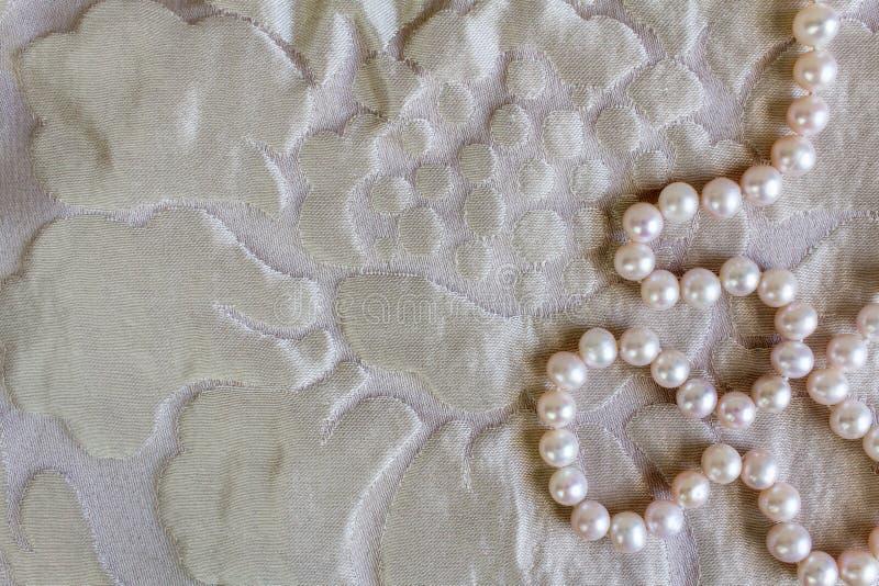 成珠状与美好的丝绸natur纹理和串的背景  免版税库存图片