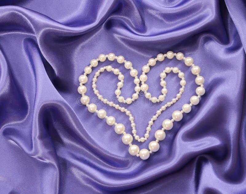 成珠状在心脏形状的项链在蓝色丝织物 免版税库存图片