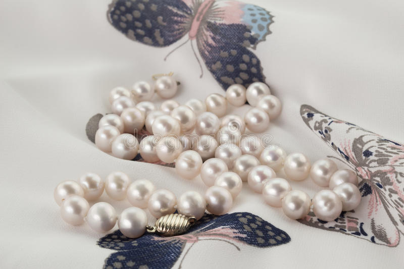 成珠状在淡色和白蝴蝶妇女的上面的项链 图库摄影