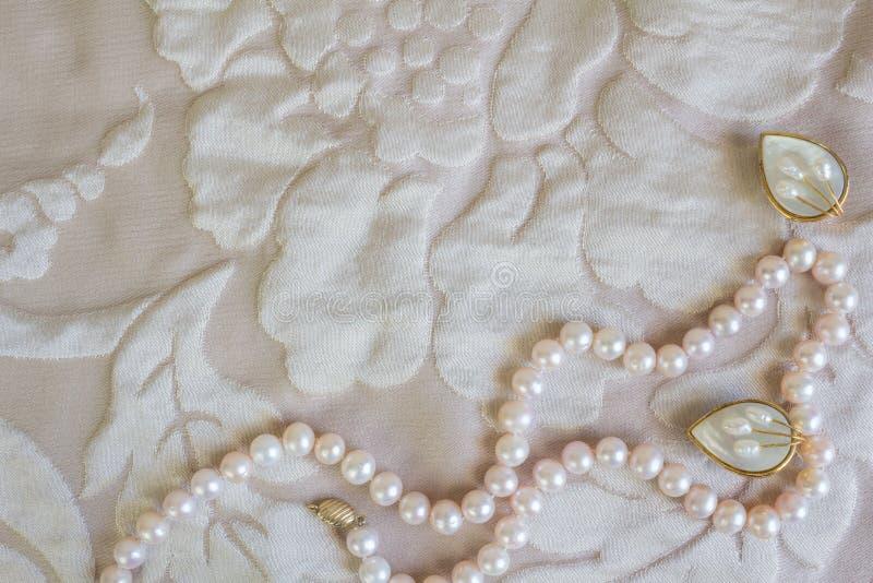 成珠状在苍白玫瑰色缎的项链和珍珠母耳环 免版税库存照片