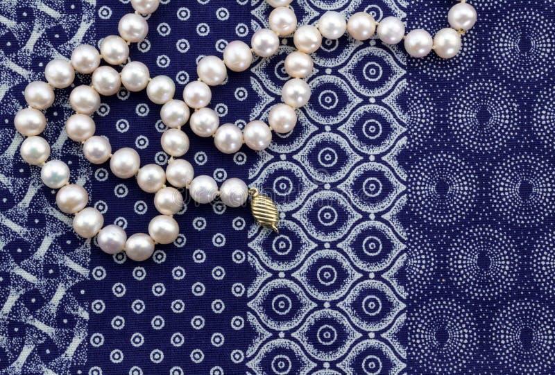 成珠状在靛蓝色和白色布料的项链背景 库存照片