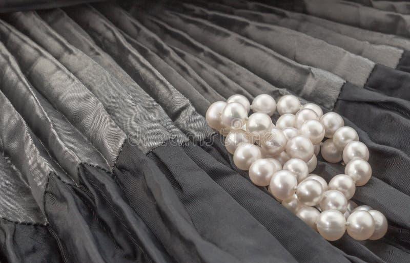 成珠状在黑和灰色被弄皱的缎背景的项链 库存照片