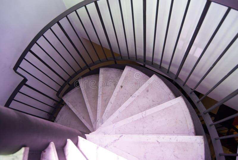 成螺旋形的一部分的marm楼梯下来 被环绕的石楼梯 库存照片