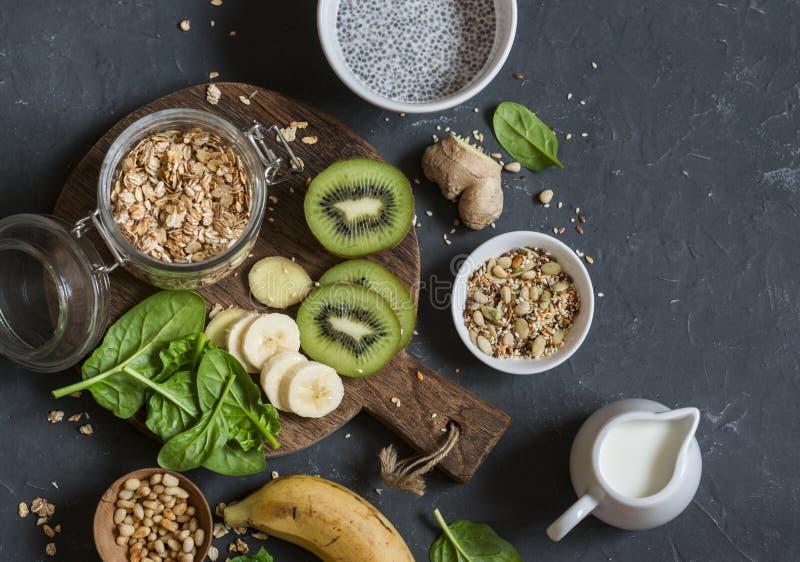 成份一顿健康早餐- chia布丁,燕麦粥,香蕉,猕猴桃,菠菜,在黑暗的背景的椰奶,顶视图 免版税库存照片