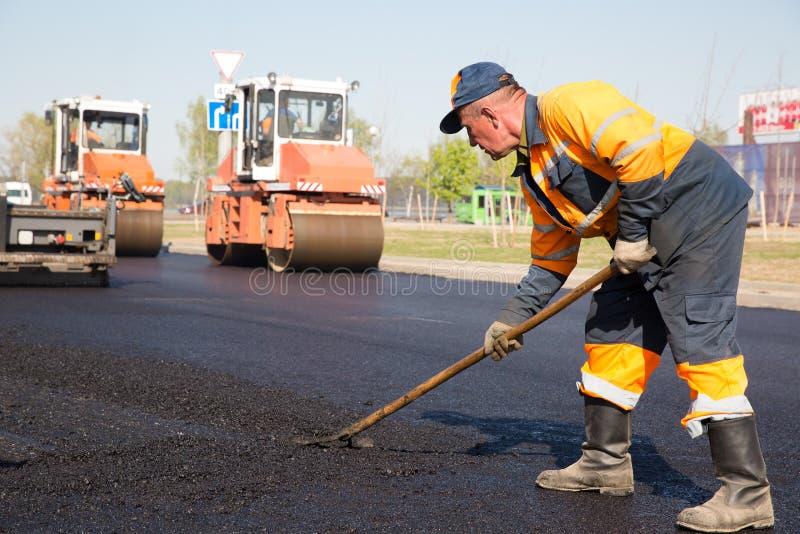 成水平新鲜的沥青的建筑工人 免版税库存图片