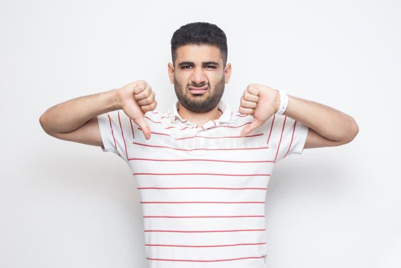 我不喜欢此 生气的有胡子的年轻人画象镶边T恤杉身分的与在反感标志姿态下的拇指和 图库摄影