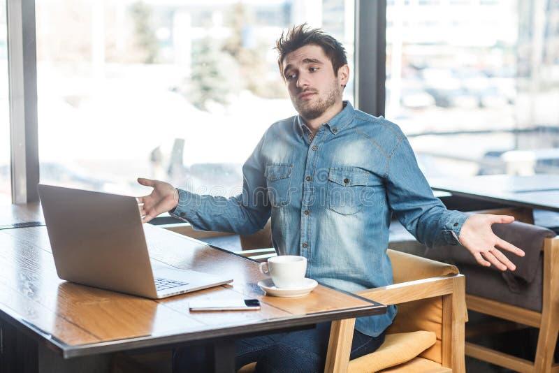 我不知道!迷茫的英俊的有胡子的年轻自由职业者侧视图画象蓝色牛仔裤衬衣的在咖啡馆和做坐 免版税库存照片