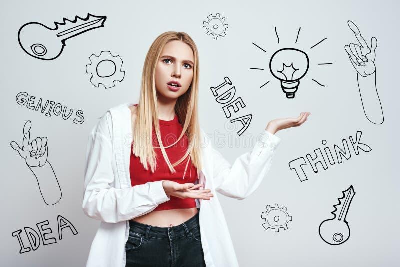 我不肯定 便衣陈列电灯泡的担心的年轻白肤金发的妇女,当站立反对灰色背景时 库存照片