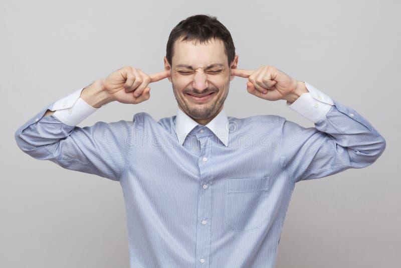 我不要听见它 在经典蓝色衬衣身分的恼怒的刺毛商人,闭合的眼睛和投入手指在耳朵 免版税库存照片