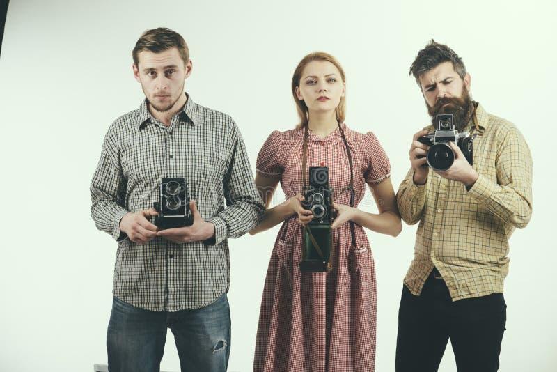 我们也许在任何时候攫取 小组有减速火箭的照相机的摄影师 减速火箭的样式妇女和人拿着模式照片照相机 库存图片