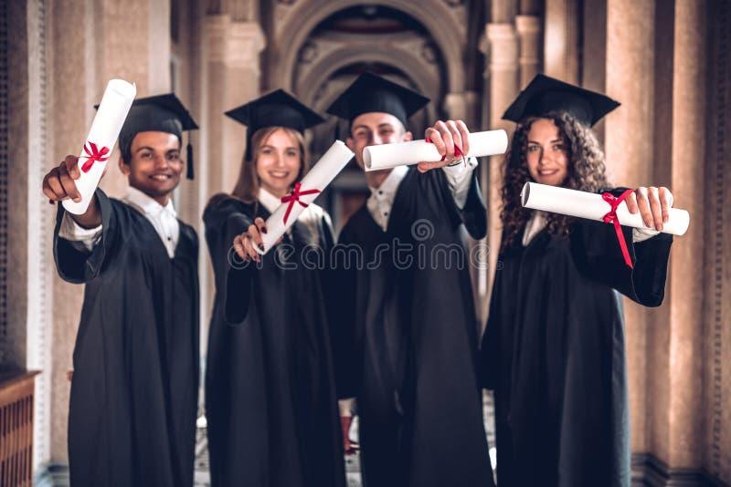 我们努力工作并且取得了结果!显示他们的文凭的小组微笑的毕业生,一起站立在大学大厅和看 免版税库存图片