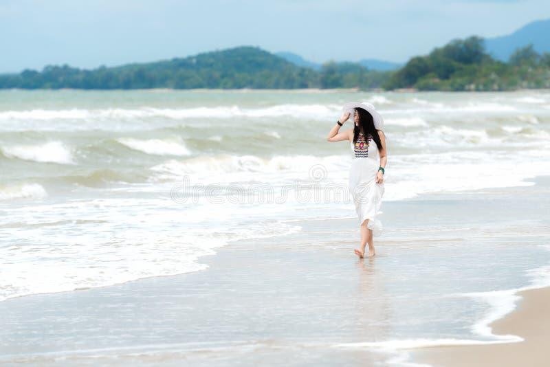 我其他看到暑假工作 放松和享受在沙子海滩的生活方式妇女摇摆,塑造有白色礼服的惊人的妇女在tr 免版税库存图片