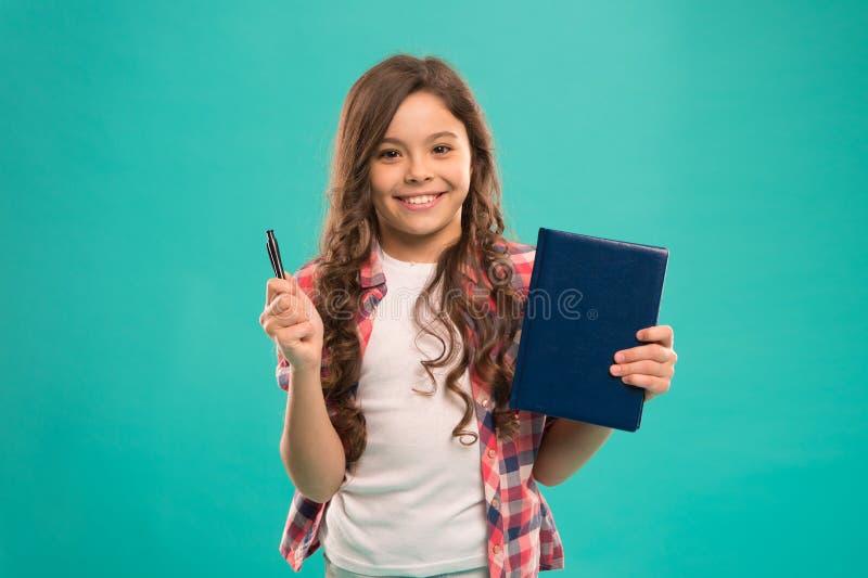 我准备好学校 儿童聪明的孩子举行笔和笔记薄 女孩逗人喜爱的愉快的面孔喜欢学习蓝色背景 孩子 免版税库存照片