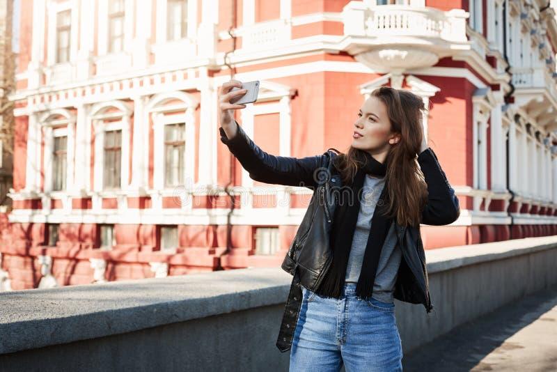 我出生对由时髦 站立在市中心的美丽的妇女室外画象,摆在,当拿着智能手机时 免版税图库摄影