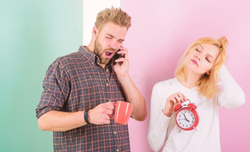 我后向工作求助 在爱的夫妇睡过头了早晨警报 妇女和人困被弄乱的头发喝早晨咖啡 库存照片