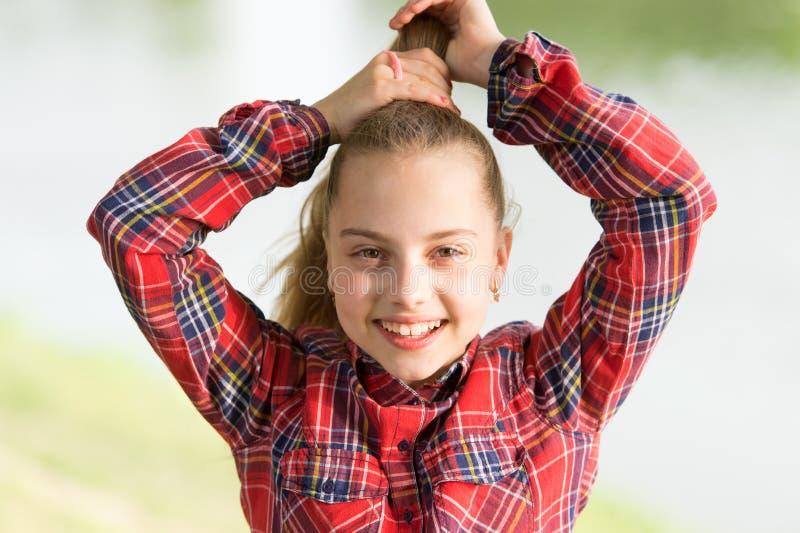 我喜爱做头发 做她的花梢马尾辫头发的逗人喜爱的小孩 称呼长的金发的可爱的小女孩 库存照片