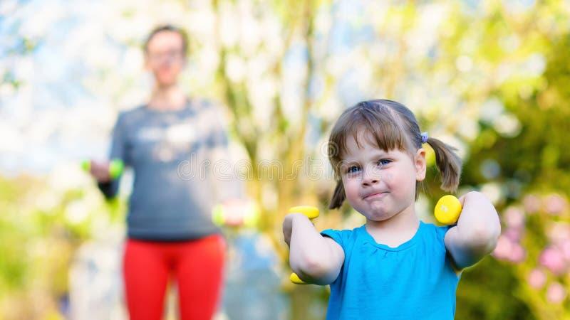 我将是坚强象我的妈妈!在她的母亲前面的愉快的小女孩举的哑铃 图库摄影