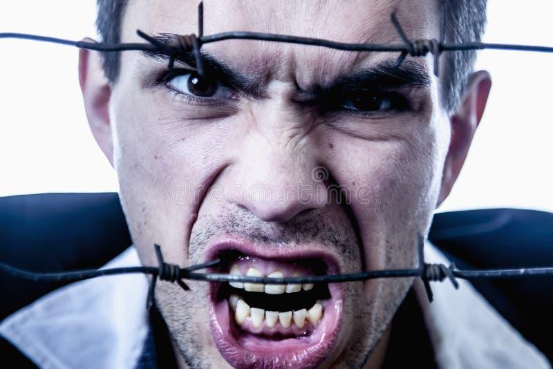 我恨社会准则!人尖叫在铁丝网后作为准备的标志战斗 库存图片