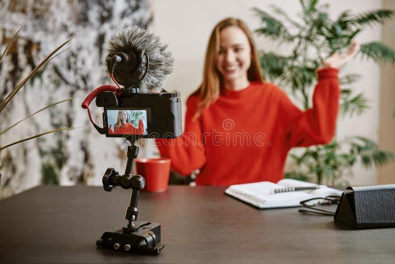 我想要您的喜欢!快乐的年轻广播画象她的vlog的一个新的讲解与三脚架登上了数字 库存照片