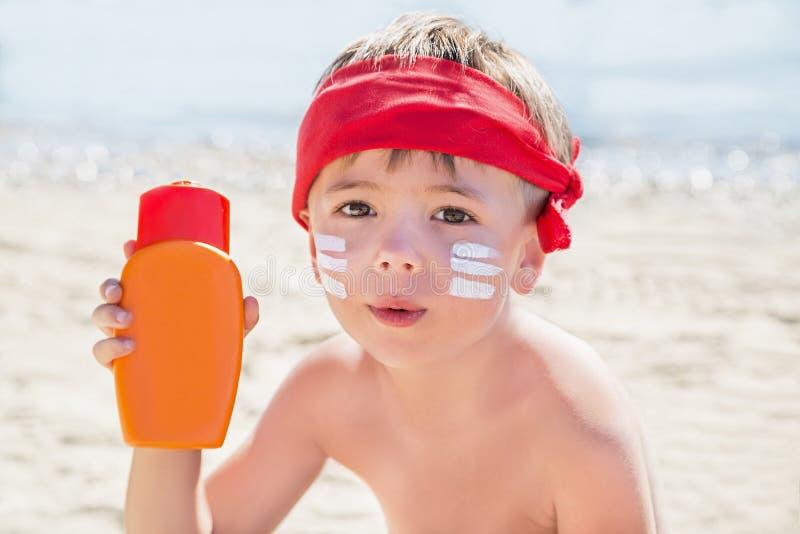 我是谁?遮光剂& x28; 晒黑lotion& x29;在海滩的暑假期间在行家男孩面孔在晒黑前 免版税库存图片