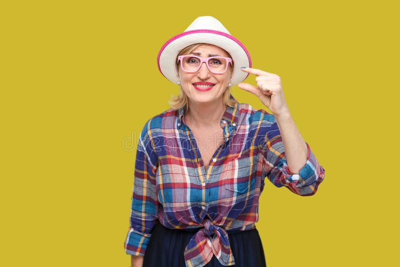 我更需要有点 喜悦的现代时髦的成熟妇女画象便装样式的与要求的帽子和的镜片站立和 免版税库存照片