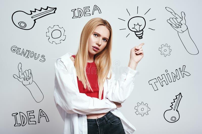 我有一个想法!便衣的俏丽的白肤金发的妇女指向指向电灯泡的,当站立反对灰色时 库存照片