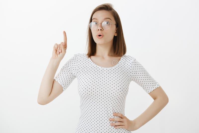 我有优良创艺 玻璃的激动的逗人喜爱的白种人女孩,握在臀部的手和举食指在尤里卡 库存照片